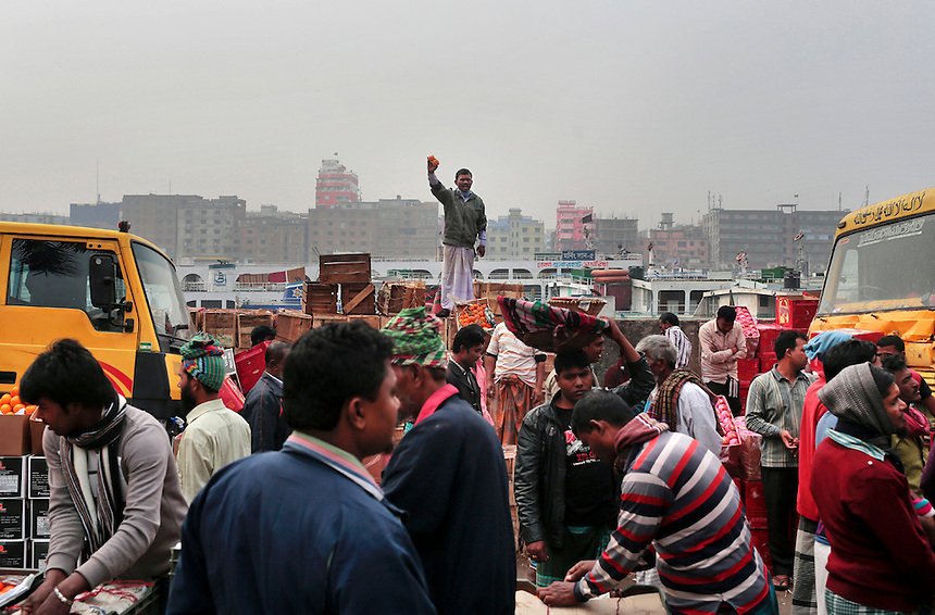 A Bangladeshi man holds fruits and shouts prices to attract customers at a wholesale market on the bank of the river Buriganga in Dhaka, Bangladesh.