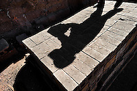 A shadow of a working child is seen on a pile of bricks at a brick factory in the outskirts of Puno, Peru, 2 August 2012. Child labour is a common practice at the artisanal brick factories, found predominantly in socially deprived areas of the urban zones. Poverty and lack of employment force parents, mainly season workers coming from rural areas of the country, to employ their own children, in an effort to ensure the livelihood for the whole family. Children aged 4-7 take part in simple jobs while children aged 8 and up tend to work regularly, same as adults. A family group, consisting of 2 adults and 2-3 children, may earn 20-25 USD per day, working almost the whole day, often in harsh climatic conditions.