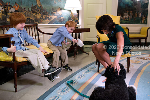 "First Lady Michelle Obama pets Bo, the Obama family dog, during a taping for ""The Ellen DeGeneres Show"" with 6-year-old Rainer Muuss, left, and his brother Atticus, 4, in the Diplomatic Reception Room of the White House, February 7, 2013..Mandatory Credit: Chuck Kennedy - White House via CNP"