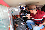 A Palestinian photographer Yasser Qudih, who was wounded on 14 May by Israeli troops as he covering a demonstration where Palestinians demand their rights to return to their home at Israel-Gaza border, lies on stretcher inside an ambulance at Erez crossing, in the northern Gaza Strip, after he return from Makassed hospital in Jerusalem where he was recovering on May 27, 2018. Photo by Mahmoud Ajour