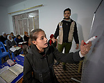 As teacher Amjad Thanoon Younis looks on, a girl writes on a whiteboard in a class to catch up with school work in war-torn Mosul, Iraq, where many didn't attend school for three years that the city was under control of the Islamic State group, also known as ISIS. The class is sponsored by RNVDO with support from DanChurchAid, a member of the ACT Alliance.