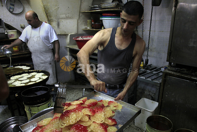 Palestinian workers make traditional sweets 'Mushabak', during celebration the Islamic holiday of Isra Mi'raj in Jerusalem on June 06, 2013. The holiday marks what Muslims believe is Prophet Mohammad's journey from Mecca to Jerusalem and it is believed to be followed by his ascension to heaven. Photo by Saeed Qaq