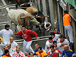 People run in front of Fuente Ymbro´s fighting bulls during the sixth bull run in the San Fermin Festival on July 12, 2014, in Pamplona, Basque Country. Every year, tens of thousands of people pack Pamplona's streets for a drunken kick-off to one os worls's best-known fiesta: the nine-day San Fermin bull-running festival. (Ander Gillenea / Bostok Photo)