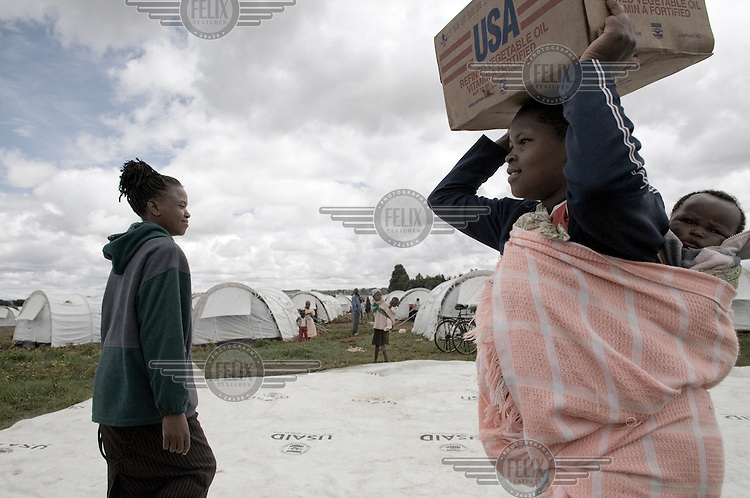 A woman carries her baby and donated food items at a camp in Eldoret. A year after a political crisis led to violence, tens of thousands of those displaced still live in the IDP (Internally Displaced Persons) camps in the Rift Valley.