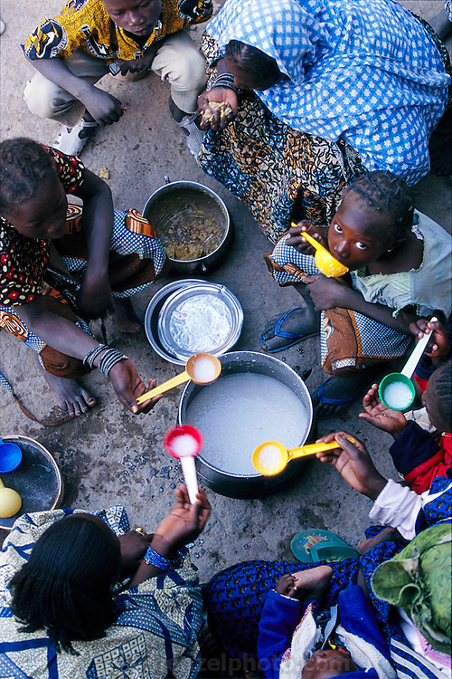 (MODEL RELEASED IMAGE). Glancing up at a visitor, Fourou: the twelve-year-old daughter of Soumana Natomo's second wife, Fatoumata, takes a momentary break from the family breakfast of thin rice porridge cooked with sour milk. Like most families in their village in Mali, the Natomos eat outdoors, sitting on low stools around a communal pot in the courtyard of their house. The Natomo family of Kouakourou, Mali, is one of the thirty families featured, with a weeks' worth of food, in the book Hungry Planet: What the World Eats.