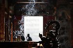 Bao-jhong Yi-min Temple, Kaohsiung -- Dragon image and wafts of incense smoke with temple custodians in the background.