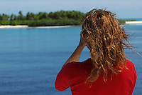 Woman taking picture of an island in the Maldives.