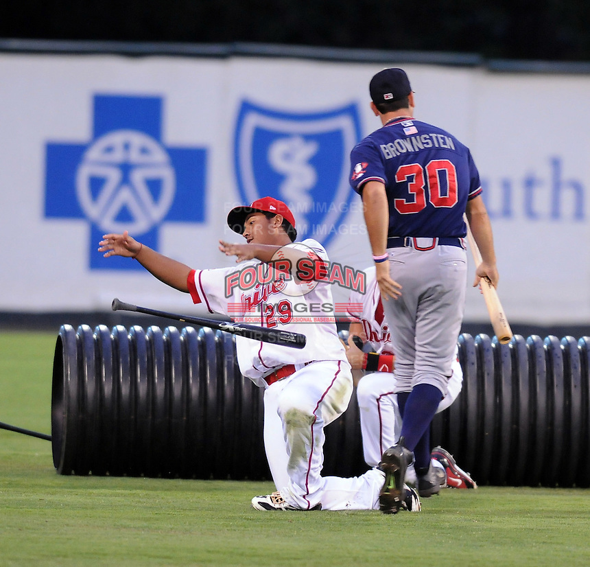 Members of the Rome Braves, including Cory Brownsten (30), right, and Greenville Drive, including Boss Moanaroa (29), left, stage a mock battle, attacking from opposite sides of the field, during a lengthy rain delay before a game on July 5, 2012, at Fluor Field at the West End in Greenville, South Carolina. (Tom Priddy/Four Seam Images)