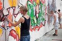 Graffiti artists at work in the Mauerpark (Berlin Wall Park).