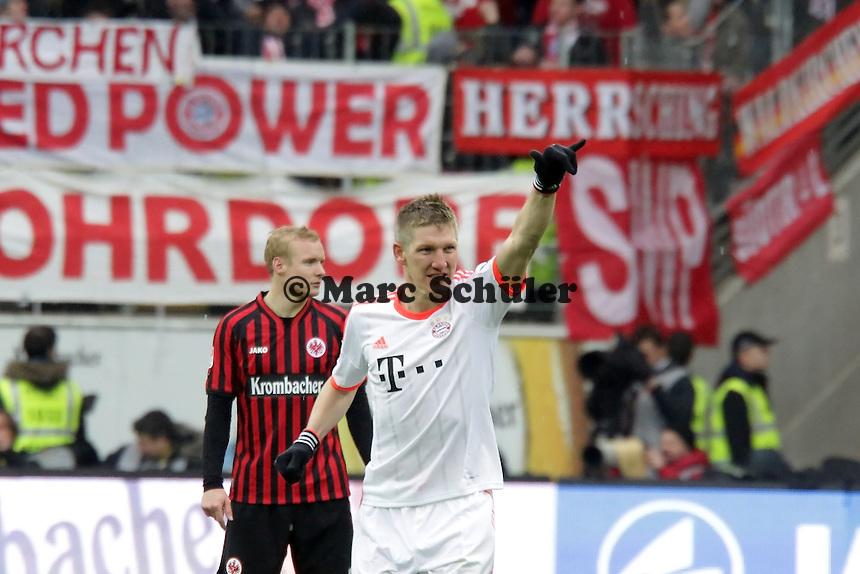 Bastian Schweinsteiger (Bayern) jubelt ueber den Treffer zum 0:1 und zeigt in Richtung der Frankfurter Fans