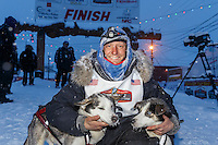 Charlie Bejna poses with his lead dogs Hawk and Duke at the Nome finish chute Friday March 14 during the 2014 Iditarod Sled Dog Race.<br />