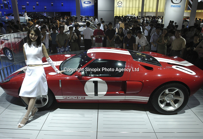 A Chinese model poses besides a Ford GT concept car at the Auto China 2004 exhibition in Beijing, China..