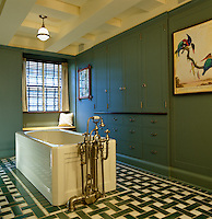 This Victorian bath with impressive plumbing sits in the centre of a bathroom with a green and white tiled floor and a wall of painted built-in cupboards and drawers