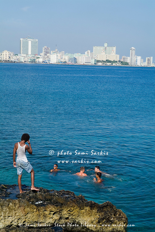 Cuban boys swimming in the Caribbean sea along the Malecón in Havana, Cuba.
