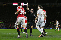 Referee Mr Jonathan Moss shows Angel Rangel of Swansea City a yellow card during the Barclays Premier League match between Manchester United and Swansea City played at Old Trafford, Manchester on January 2nd 2016
