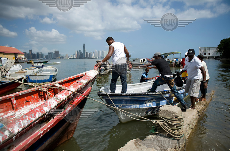 Fishermen board their boats moored at the fishing harbour. The city skyline is visible in the background..