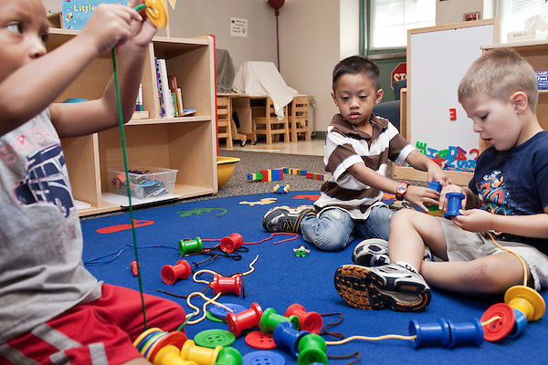 September 14, 2011. Raleigh, NC. . (right to left) Tyler Roth and Gian David De La Rosa play with oversized spools, buttons and thread.. Project Enlightenment, a public pre-kindergarten program for at risk children, has been threatened with closure due to state wide budget cuts..