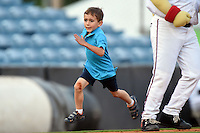 Young fan races Nashville Sounds mascot Ozzie during an on field promotion in between innings during a game against the Omaha Storm Chasers on May 19, 2014 at Herschel Greer Stadium in Nashville, Tennessee.  Nashville defeated Omaha 5-4.  (Mike Janes/Four Seam Images)