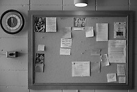 A bulletin board outside the chapel holds hermitage announcements and prayer requests.