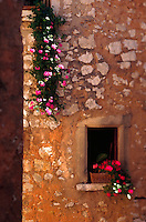 Rustic stone wall and potted flowers. France.