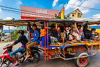 A motorcycle pulls a kind of gerryrigged homemade bus, outside Phnom Penh, Cambodia.