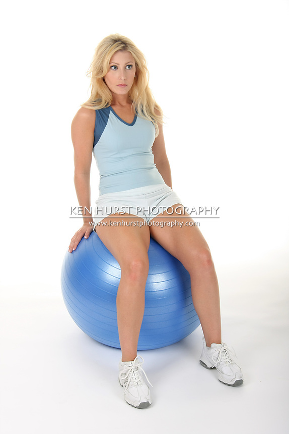 Attractive young blonde woman exercising on an exercise ball.