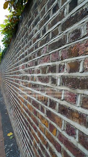London, England. View along a brick wall.