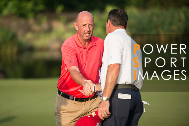 Gary McAllister (in red) and Rich Beem (in white) rejoice at the end of their game during the World Celebrity Pro-Am 2016 Mission Hills China Golf Tournament on 23 October 2016, in Haikou, Hainan province, China. Photo by Marcio Machado / Power Sport Images