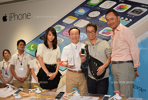 September 20, 2013, Tokyo, Japan - President Kaoru Kato, center, of NTT Docomo hands the very first iPhone to one Hidenori Kato, second from right, at a Docomo shop in Tokyo as sales of Apple's latest iPhones begins across Japan on Friday, September 20, 2013. Flanking the two are, actors Ken Watanabe and Maki Horikita.<br /> <br /> After consistently losing its market share to its competitors - Softbank and KDDI - with the Apple smartphones in their lineups, the nation's leading mobile phone provider has now joined its rivals in selling iPhones. Docomo's move will likely deal a blow to Japanese smartphone manufacturers such as Sony Corp., Fujitsu Ltd. and Sharp Corp.  (Photo by Natsuki Sakai/AFLO)