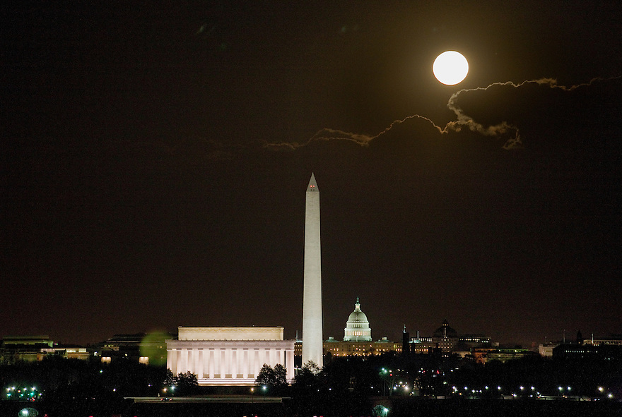 A full moon rises over the Lincoln Memorial, Washington Monument, and United States Capitol at night in Nation's Capital, Washington, DC.