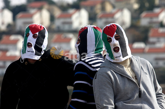 Palestinian demonstrators take a break during clashes with Israeli soldiers during a protest against the expansion of the nearby Jewish settlement of Halamish in the West Bank village of Nabi Saleh, near Ramallah, Friday, Feb. 3, 2012. Photo by Issam Rimawi