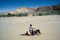 A farmer on is hors crossing the Harï Rüd river on the road to the Menar e Jam in the Ghor province - Afghanistan..From western Afghan capital Herat to the former capital of the Ghorides Empire Fîrûzkôh, next to the Menar e Jam..-The full text reportage is available on request in Word format