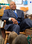 "Photo by Phil Grout..Congressman Elijah Cummings gives the first graders at Clarksville Elementary a lesson from Dr. Seuss' Foot Book.  ""And some feet.are big like mine,"" the Congressman said as he quickly leaned back in.his rocking chair and held up his left foot.  It was all part of the Read Across America program."