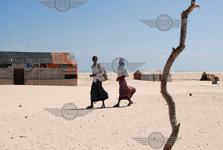 Two young men walk through the remote coastal village of Eyl.