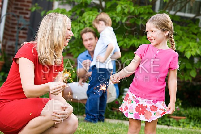 Series with a Caucasian family outdoors, on a summer day - mother, father, son, daughter.  Overall a July 4th holiday theme.  Playing with sparklers, dinner on the porch and American flags.