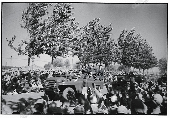 After waiting for days in and around Tiananmen Square for a glimpse of the Great Helmsman, crowds cheer and wave Little Red Books as he passes in his jeep. Mao is standing behind the driver; behind him is his personal physician, Li Zhisui; to Mao's left is General Yang Chengwu; and beside the driver is Mao's chief of staff, Wang Dongxing. Beijing, 18 October 1966