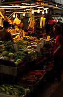 A vegetable stall under lights in the evening in a market street, Hong Kong.