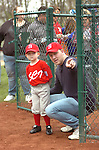 A dad and coach gives last minute instructions before introductions on opening day of Little League