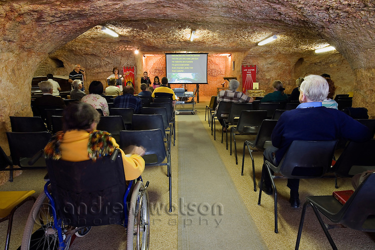 Sunday mass in the Catacomb Church - one of five underground churches in the opal mining town of Coober Pedy.  Originally built in 1977 the church is cut out of the sandstone walls in the shape of a cross.  Coober Pedy, South Australia, AUSTRALIA.