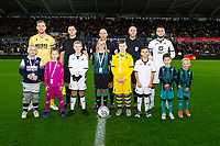 Alex Pearce of Millwall and Matt Grimes of Swansea City with mascots during the Sky Bet Championship match between Swansea City and Millwall at the Liberty Stadium in Swansea, Wales, UK. Saturday 23rd November 2019