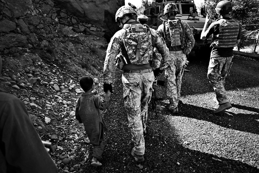 A member of 3rd Platoon, Dagger Company, 2-12th Infantry walks with a child while other members of the company talk to local villagers about damage caused to houses by ordnance fired into the village of Matin, in the Pesh Valley, Kunar Province, Afghanistan, Sunday, Sept 27, 2009.