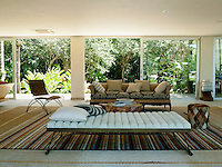 A modern chaise in the living area is matched with a wicker chair, a leather stool and a sofa on a striped rug
