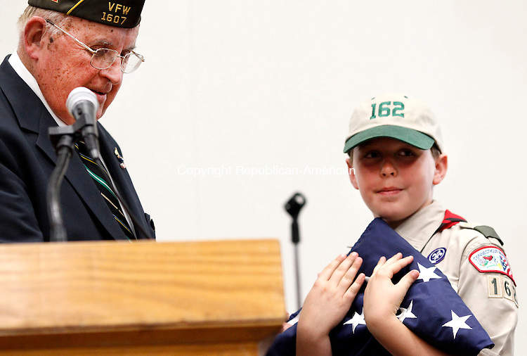 Southbury, CT- 14 June 2013-061413CM02- Harmon Andrews, left, a retired U.S. Army Captain and veteran of the Korean War, hands over a flag to Jason Davis, 10, and a Boy Scout with Troop 162 of Southbury, during a Flag Day ceremony at the Southbury Town Hall Friday afternoon. Flag Day commemorates the adoption of the United States flag which occurred on June 14, 1777. The United States Army also celebrates the Army's birthday on this date.    Christopher Massa Republican-American