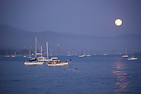 Moon reflecting at dusk with boats in Santa Barbara, California harbor