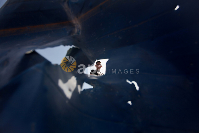 "A Palestinian man is pictured through a Piece of metal as he inspects the rubble of a training camp used by Hamas after it was hit by an Israeli missile strike in Gaza City, early Thursday, June 19, 2014. The Israeli military said five rockets were fired from Hamas-controlled Gaza into Israel. One rocket struck a house in southern Israel, causing damage but no injuries. Early Thursday, Israel responded with a series of airstrikes on ""terror activity"" sites in Gaza. It said ""direct hits"" were confirmed. There were no immediate reports of injuries. Photo by Ashraf Amra"