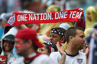 A USA fan holds a scarf that says 'One Nation. One Team'