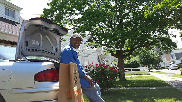WATERBURY, CT - June 10, 2015 - 061015AL01 - Frizell Williams sits in front of his home on Sycamore Lane in Waterbury, which is being used as a detour while the intersection of Plank Road and Harpers Ferry Road is closed due to the widening of Interestate 84. The highway reconstruction project, which began in April and is expected to take five years to complete, has increased the volume of traffic on many streets, including those in the White City neighborhood.
