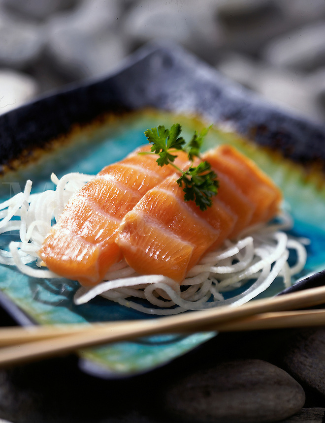 Salmon sashimi on japanese plate with chopsticks soft focus.