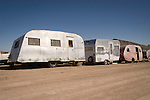Canned ham travel trailers abandoned by junk yard.