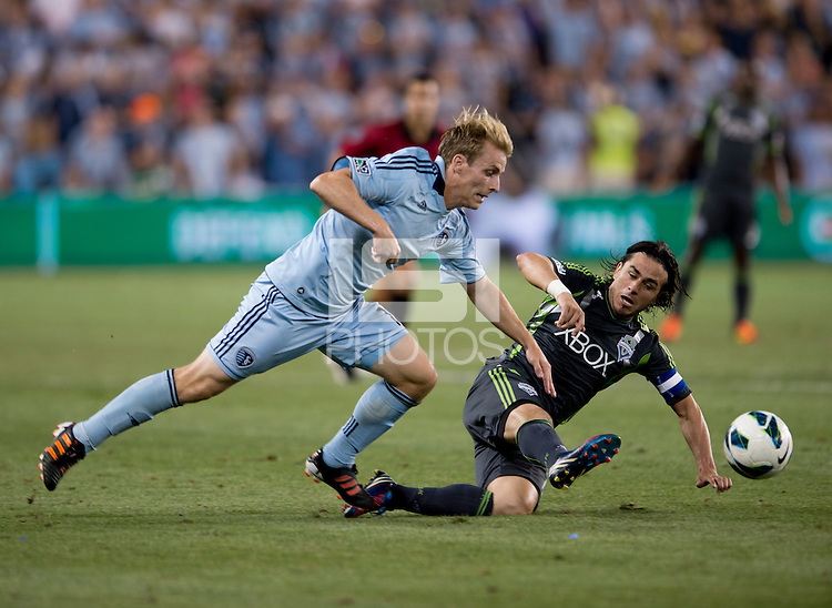 Seth Sinovic (16) of Sporting Kansas City is fouled by Mauro Rosales (10) of the Seattle Sounders during the game at Livestrong Sporting Park in Kansas City, Kansas.   Sporting Kansas City won the Lamar Hunt U.S. Open Cup on penalty kicks after tying the Seattle Sounders in overtime.